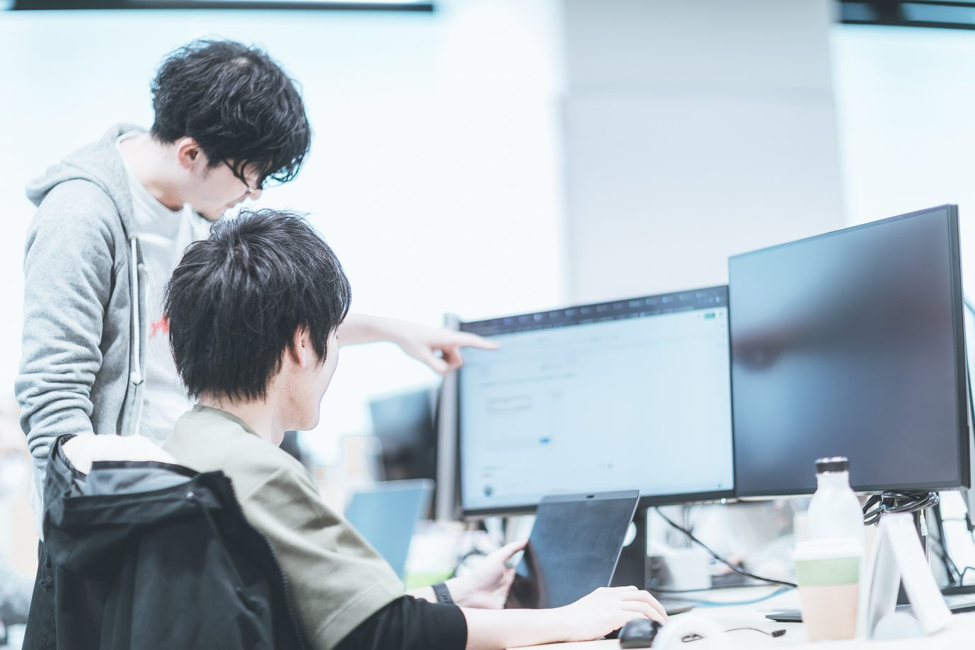 Two DeNA employees collaborate over a computer screen.