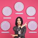Woman standing in front of a pink wall pointing at different clocks