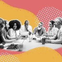 characteristics of high-performing teams hero image of people gathered around a table working