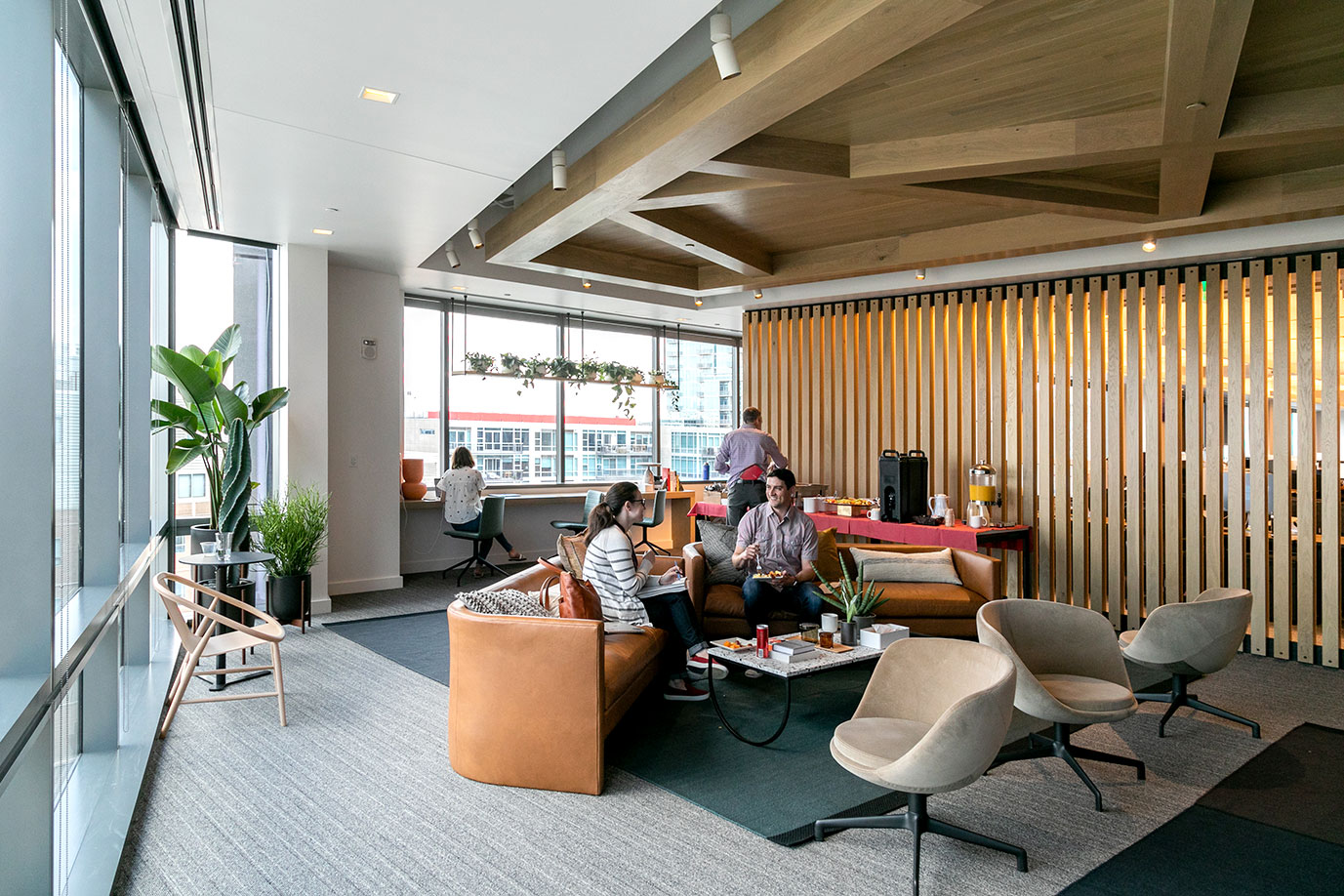 An open office area space featuring big windows, wooden architectural details in a West Coast style of design, and two employees reposing on a plush sofa.