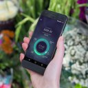 Hand holds Starling Bank's mobile application for an article about how Starling uses Slack