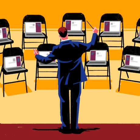 A conductor motioning to rows of chairs with laptops propped on them